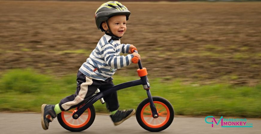 Kid on a bike with helmet on.